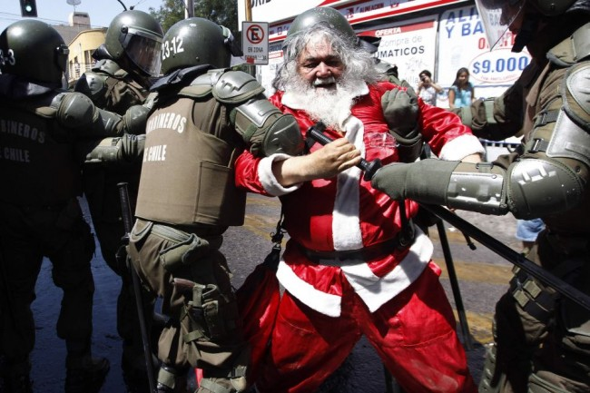A demonstrator dressed as Santa Claus is arrested by riot policemen during clashes with student protesters in Santiago
