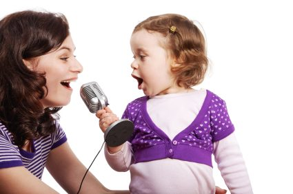 Mother and her little daughter sing into the microphone, looking